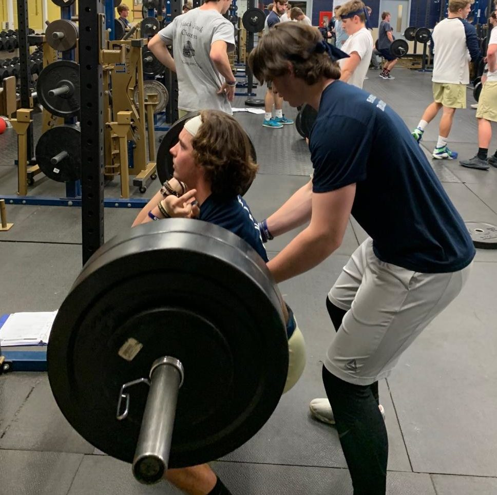 Tyler Monk lifting for the 40/40 challenge while being spotted by Wes Ward