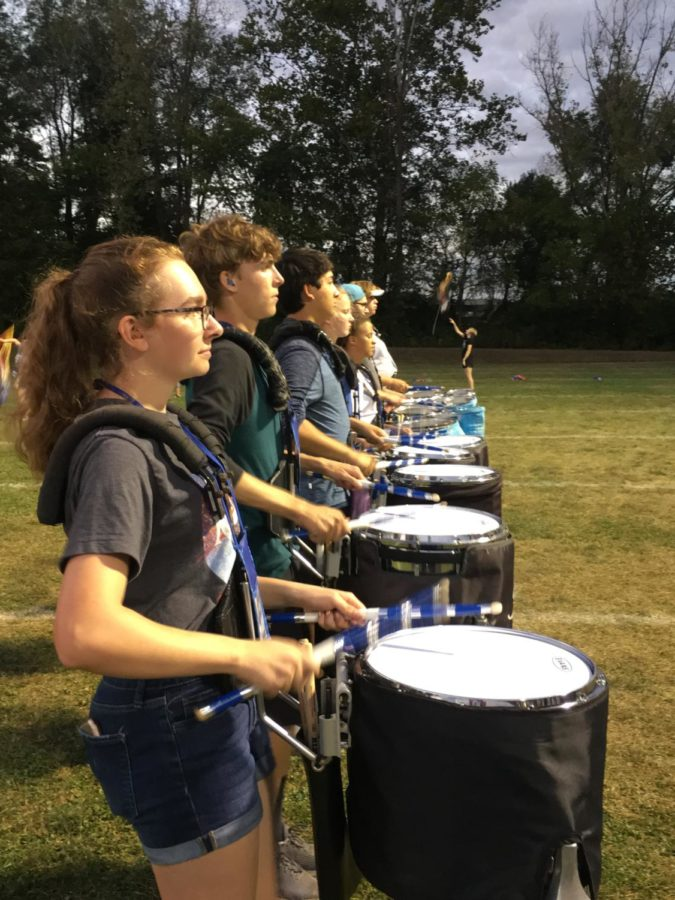 Percussionists march and drum to the show.