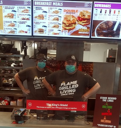 Burger King employees behind a protective plastic shield.